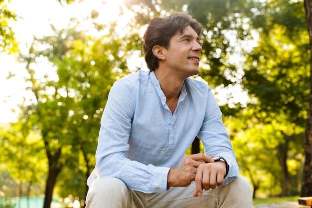 彼のスマートウォッチを調整する笑顔の若いカジュアルな男