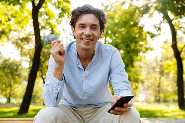 Smiling young casual man holding mobile phone