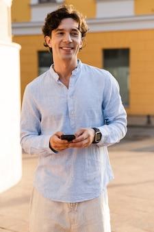 Улыбающийся молодой случайный человек, держащий мобильный телефон