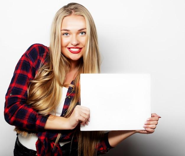 空白の看板を示す分離されたホワイトスペースを笑顔の若いカジュアルスタイルの女性