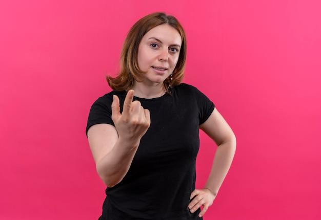 La giovane donna casuale sorridente che gesturing viene qui con la mano sulla vita sullo spazio rosa isolato con lo spazio della copia