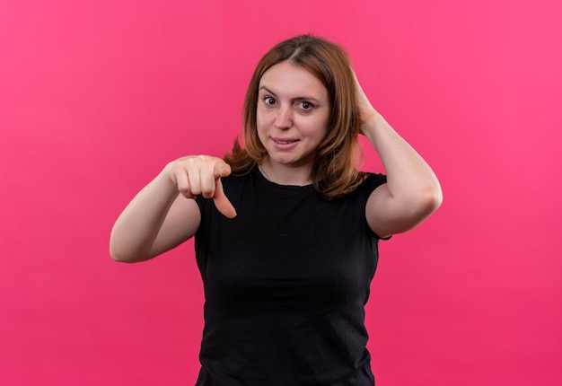 Sorridente giovane donna casual che punta con la mano dietro la testa su uno spazio rosa isolato