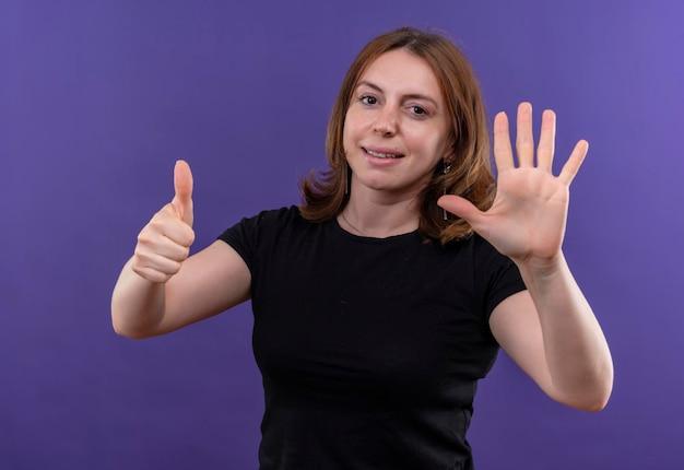 Giovane donna casuale sorridente che mostra sei sullo spazio viola isolato