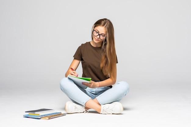 白い壁に座っている間彼女のメモ帳に書く若いカジュアルな女性の笑顔
