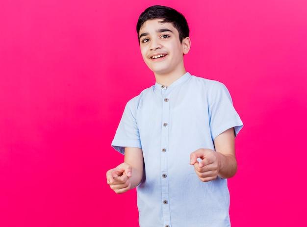 Giovane ragazzo caucasico sorridente che ti fa gesto isolato sulla parete cremisi con lo spazio della copia