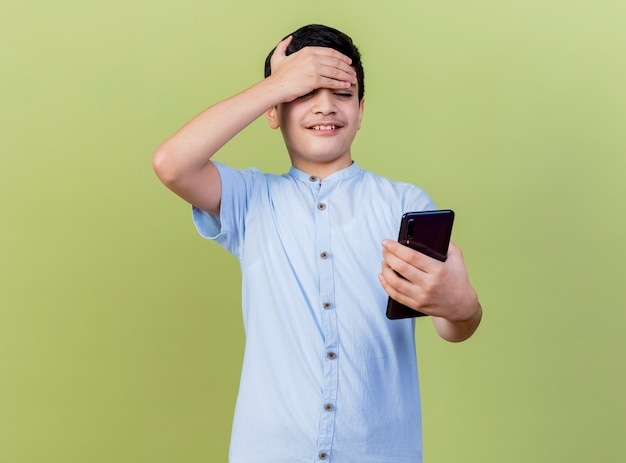 젊은 백인 소년 들고 웃 고 복사 공간 올리브 녹색 배경에 고립이 마에 손을 유지하는 휴대 전화를보고