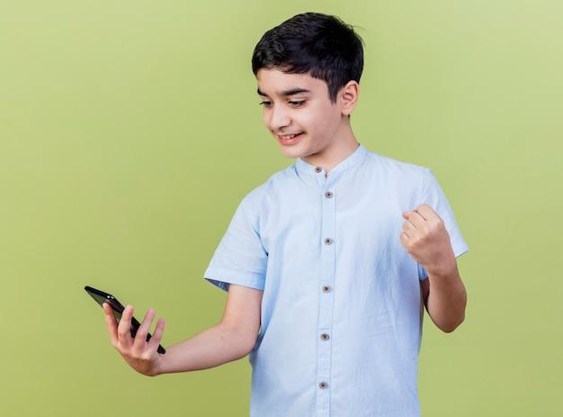 Sorridente giovane ragazzo caucasico tenendo e guardando il telefono cellulare facendo sì gesto isolato su sfondo verde oliva