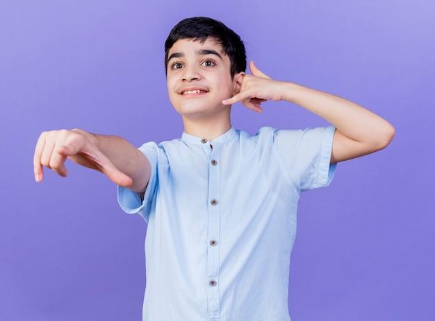 紫色の壁に分離された通話ジェスチャーを見てまっすぐに指している若い白人の少年の笑顔