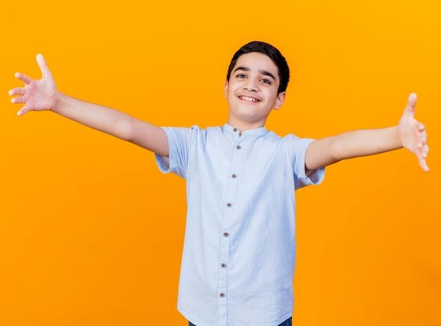 주황색 배경에 고립 된 카메라를보고 두 팔을 벌려 누군가를 인사하는 카메라를보고 웃는 어린 백인 소년