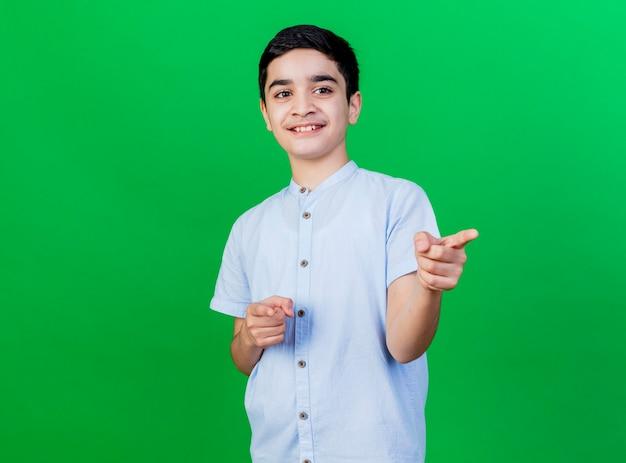 녹색 배경 복사 공간에 고립 된 제스처를 하 고 측면을보고 웃는 어린 백인 소년