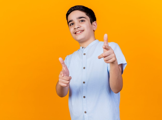 Sorridente giovane ragazzo caucasico che guarda l'obbiettivo che ti fa gesto isolato su priorità bassa arancione con lo spazio della copia