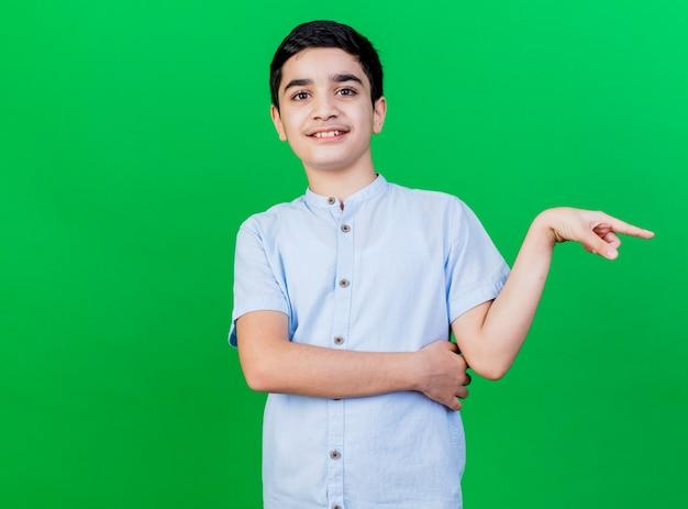 コピースペースと緑の壁に隔離された側を指している若い白人の少年の笑顔