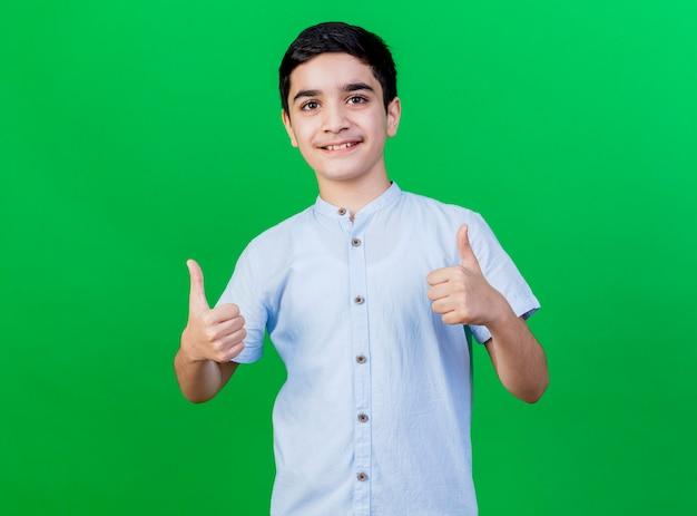 Sorridente giovane ragazzo caucasico che mostra i pollici in su isolato sulla parete verde