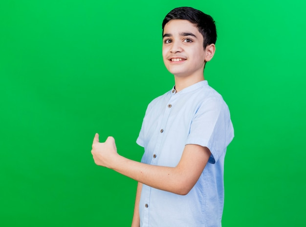 Smiling young caucasian boy standing in profile view pointing at side looking at camera isolated on green background with copy space