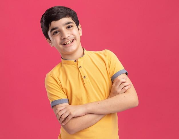 ピンクの壁に分離された閉じた姿勢で立っている若い白人少年の笑顔