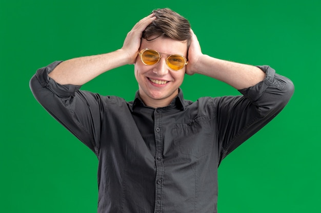 Smiling young caucasian boy in sun glasses putting hands on his head and looking at camera