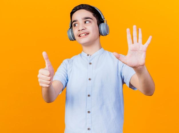 오렌지 배경에 고립 된 손으로 6을 보여주는 측면을보고 헤드폰을 쓰고 웃는 어린 백인 소년