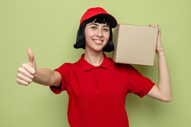 Sorridente giovane ragazza caucasica delle consegne che tiene una scatola di cartone sulla spalla e fa il pollice in alto