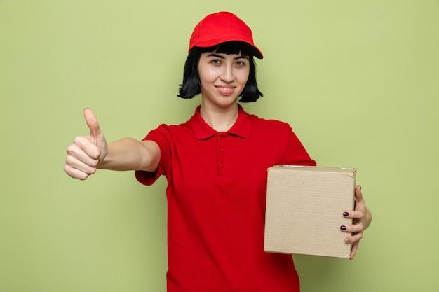 Sorridente giovane ragazza delle consegne caucasica che tiene in mano una scatola di cartone e fa il pollice in alto
