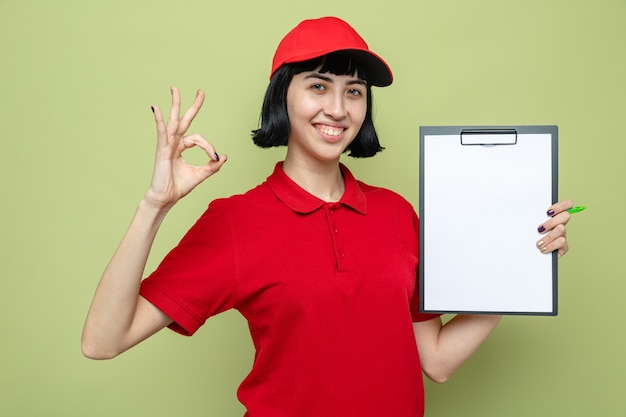 Smiling young caucasian delivery girl holding clipboard and gesturing ok sign