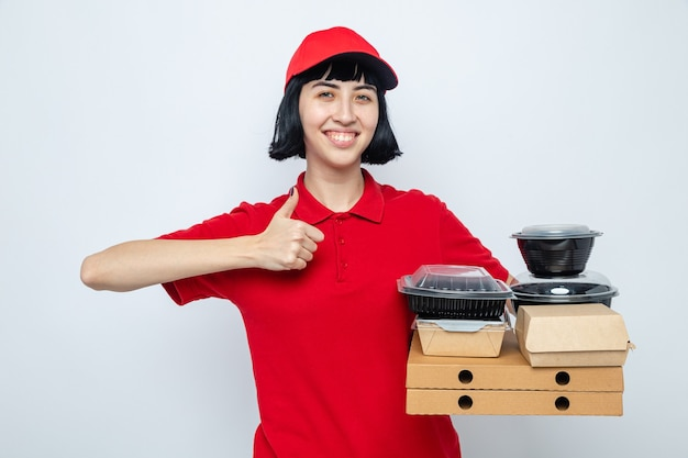 Smiling young caucasian delivery girl holding food containers and packaging on pizza boxes thumbing up