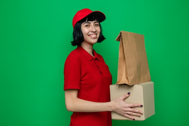Smiling young caucasian delivery girl holding food packaging on cardboard box
