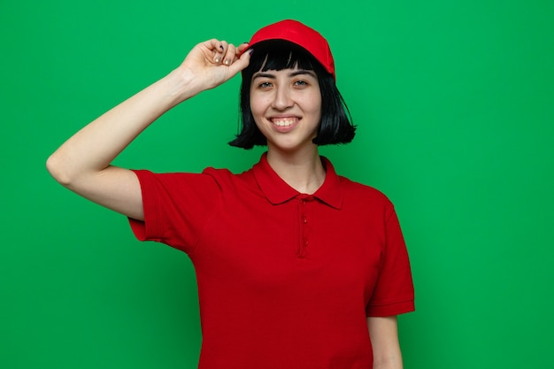 Sorridente giovane ragazza delle consegne caucasica che tiene il suo berretto e