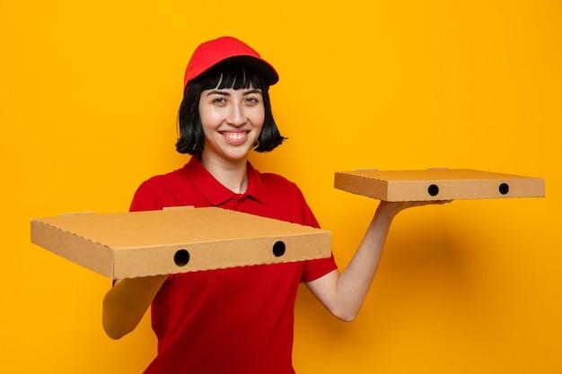 Sorridente giovane ragazza delle consegne caucasica che tiene scatole per pizza sulle mani