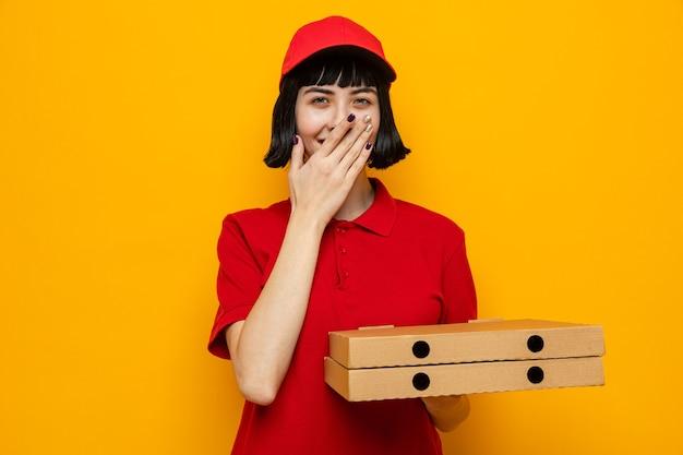 Sorridente giovane ragazza delle consegne caucasica che tiene in mano scatole per pizza e si mette la mano sulla bocca