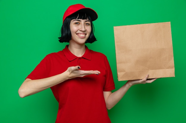 Smiling young caucasian delivery girl holding and pointing at paper food packaging with hand