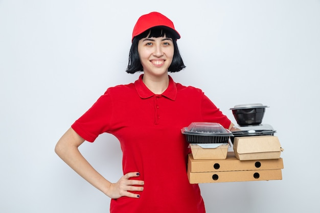 Smiling young caucasian delivery girl putting hand on her waist and holding food containers and packaging on pizza boxes