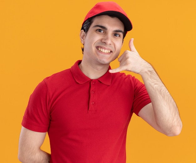 Smiling young caucasian delivery man in blue uniform and cap  doing call gesture isolated on orange wall