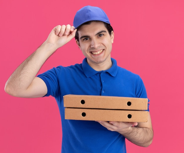Smiling young caucasian delivery man in blue uniform and cap grabbing his cap holding pizza packages isolated on pink wall