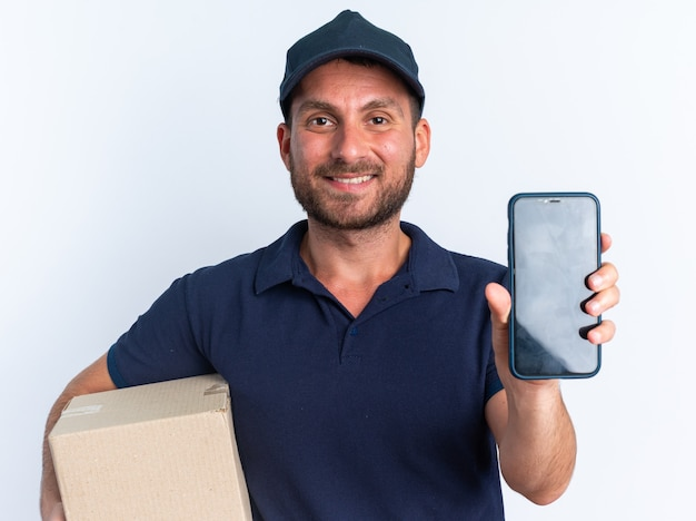 Smiling young caucasian delivery man in blue uniform and cap holding cardboard box looking at camera stretching out mobile phone towards camera isolated on white wall