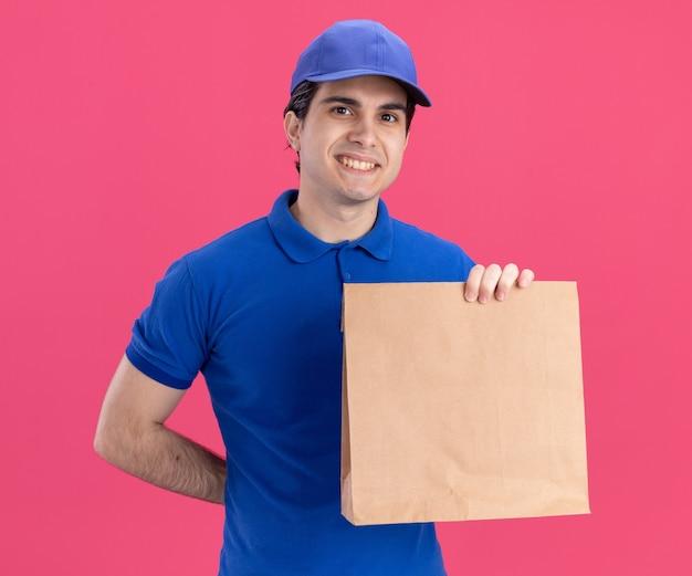 Sorridente giovane fattorino caucasico in uniforme blu e berretto che tiene un pacchetto di carta tenendo la mano dietro la schiena