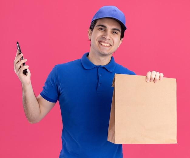 Sorridente giovane caucasico fattorino in uniforme blu e cappuccio con pacchetto di carta e telefono cellulare isolato su parete rosa on