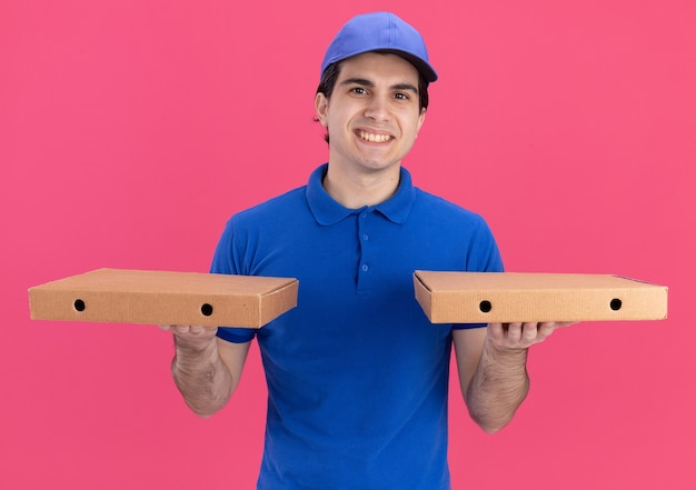 Smiling young caucasian delivery man in blue uniform and cap holding pizza packages isolated on pink wall