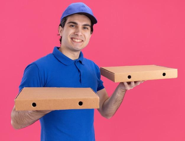 Sorridente giovane fattorino caucasico in uniforme blu e berretto con pacchi di pizza isolati su parete rosa