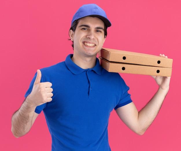 Sorridente giovane fattorino caucasico in uniforme blu e berretto in possesso di pacchetti di pizza che mostra pollice in su isolato su parete rosa