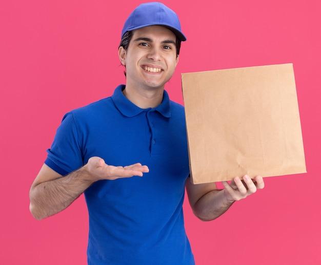 Sorridente giovane fattorino caucasico in uniforme blu e berretto che tiene e indica con la mano il pacchetto di carta