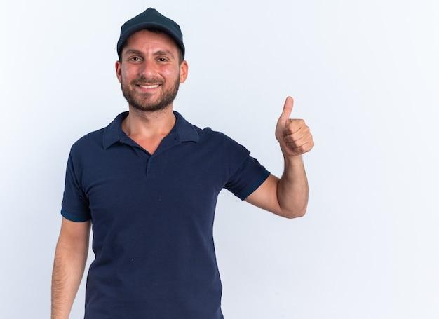 Sorridente giovane fattorino caucasico in uniforme blu e berretto che mostra pollice in su