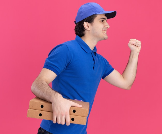 Smiling young caucasian delivery man in blue uniform and cap standing in profile view holding pizza packages doing knocking gesture looking straight isolated on pink wall