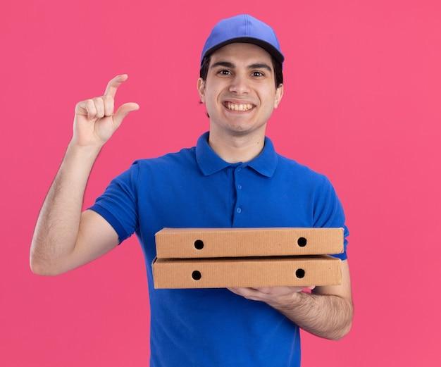 Улыбающийся молодой кавказский доставщик в синей форме и кепке, держащий пакеты с пиццей, демонстрирующий небольшой жест, изолированный на розовой стене