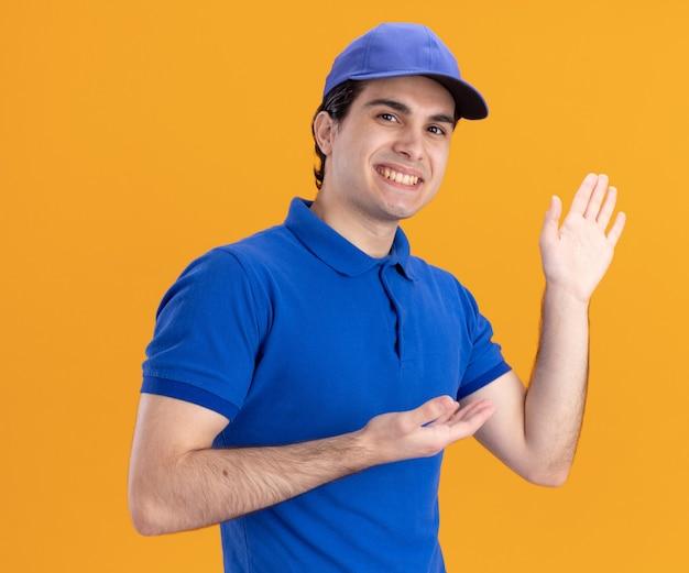 Улыбающийся молодой кавказский курьер в синей форме и кепке показывает пустую руку, указывающую на него