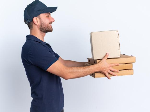 Улыбающийся молодой кавказский курьер в синей форме и кепке, стоящий в профиле, протягивая пакеты для пиццы и картонную коробку, глядя на них