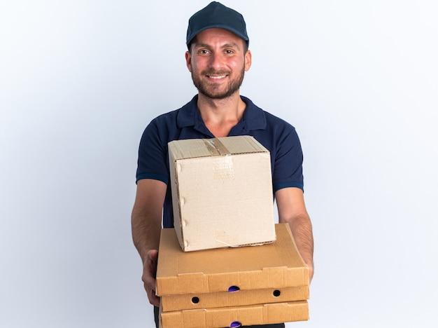 Улыбающийся молодой кавказский курьер в синей форме и кепке протягивает пакеты с пиццей и картонную коробку к камере