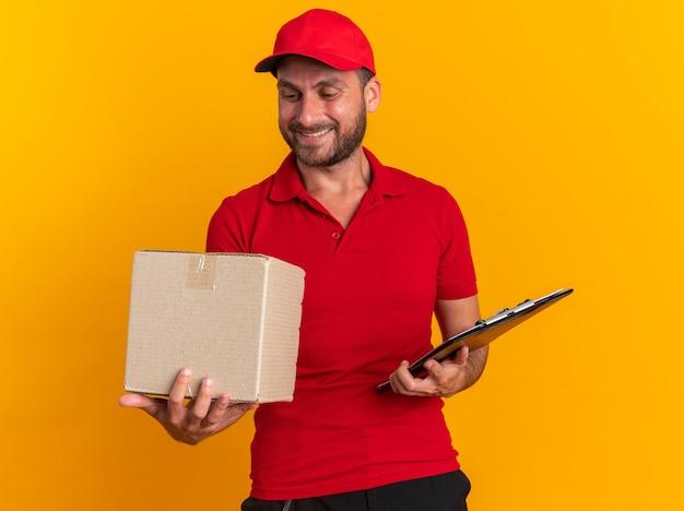 빨간 유니폼을 입은 웃고 있는 백인 배달원과 마분지 상자와 클립보드를 들고 주황색 벽에 격리된 판지 상자를 보고 있는 모자 프리미엄 사진