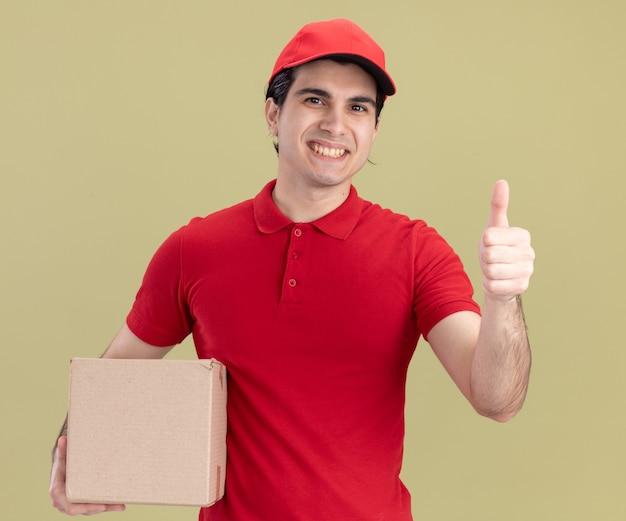빨간 유니폼을 입은 웃고 있는 백인 배달원과 올리브 녹색 벽에 고립된 엄지손가락을 보여주는 카드박스를 들고 있는 모자