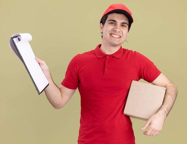 赤い制服と帽子を保持しているカードボックスの脇の下とクリップボードの若い白人配達人の笑顔