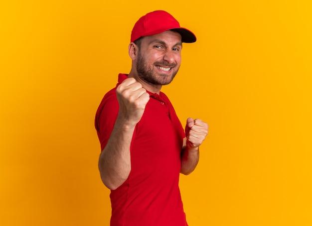 빨간 유니폼을 입은 웃고 있는 백인 배달원과 프로필 보기에 서 있는 모자는 복사 공간이 있는 주황색 벽에 격리된 권투 제스처를 하는 카메라를 바라보고 있습니다.